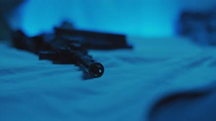 Close up of M16 rifle lying on a bed. Military, PTSD soldier concept. Cinematic handheld shot.