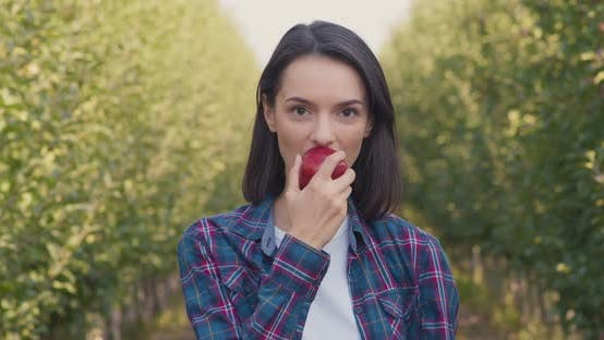 Young Woman Biting Fresh Natural Apple Standing in Own Fruit Garden and Smiling