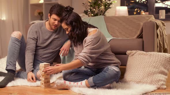 Cover Image for Happy Couple Playing Block-stacking Game at Home