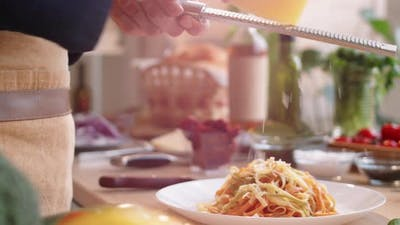 Hands of Male Cook Grating Cheese over Cooked Pasta