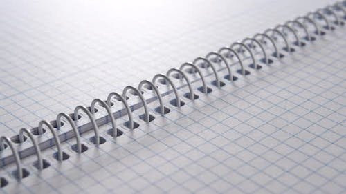 Notepad with white metallic spiral binding of blank checkered pages