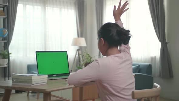 Teenager-Mädchen, das an ihrem Schreibtisch sitzt und lernt online auf einem Laptop mit grünem Mock-Up