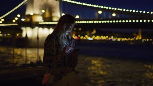 Thumbnail for Woman scrolling on her phone, at night