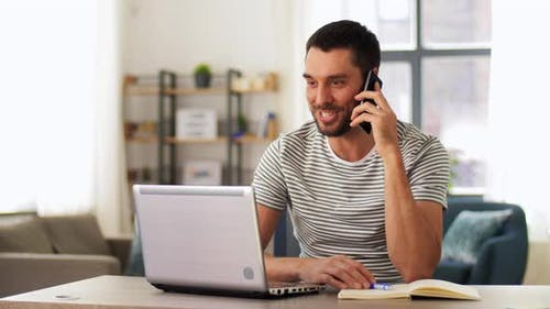 Man with Laptop Calling on Phone at Home Office