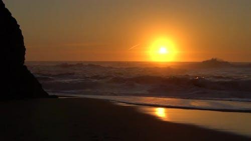 Sunset Shining Above Small  Waves Crashing on the Beach