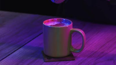 Barista Sprinkles Coffee on Top with Powdered Cinnamon