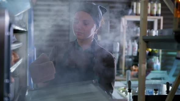 Thumbnail for Kleine Unternehmen, weibliche Bäckerin in Handschuhen und Uniform nimmt frisch gebackene Brötchen aus heißem Ofen, Gebäck