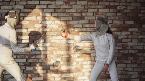 Man and Woman Are Fencing in a Training Hall, Hitting with Rapiers
