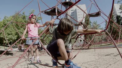 Long Shot of Boy and Girl Climbing Attractions in Amusement Park