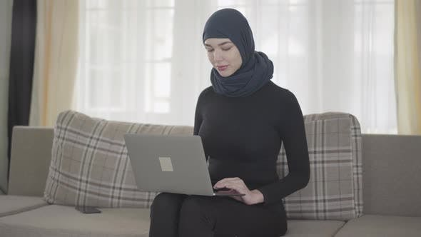 Thumbnail for Young Muslim Woman Was Working or Chatting By Laptop and After Somebody Called Her By the Smartphone