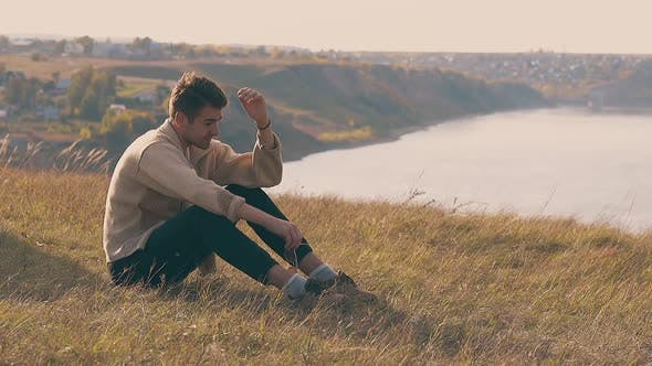 Frustrated Guy in Jeans and Pullover Sits on River Bank