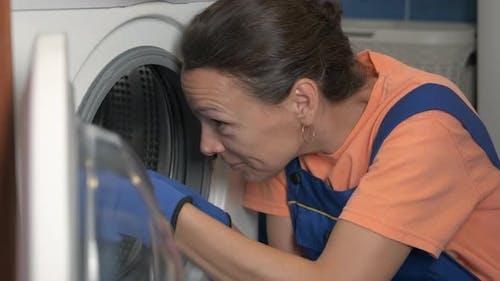 The Female Is Repairing the Washing Machine