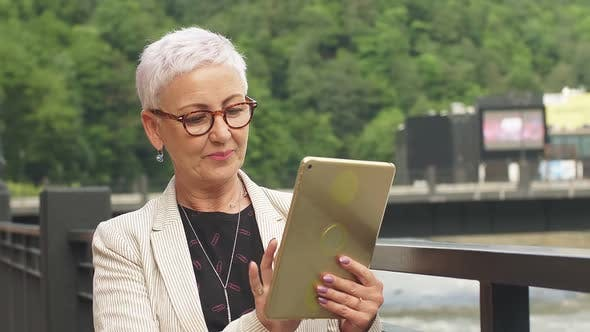Cover Image for Elegant Adult Lady Uses Tablet in Outdoor