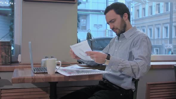 Thumbnail for Exhausted Businessman in a Coffee Shop Searching in Documents