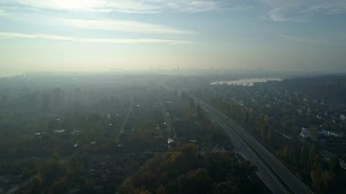 Aerial Drone Footage. Fly Over Autobahn Near Downtown with City on Horizon in Light Fog.