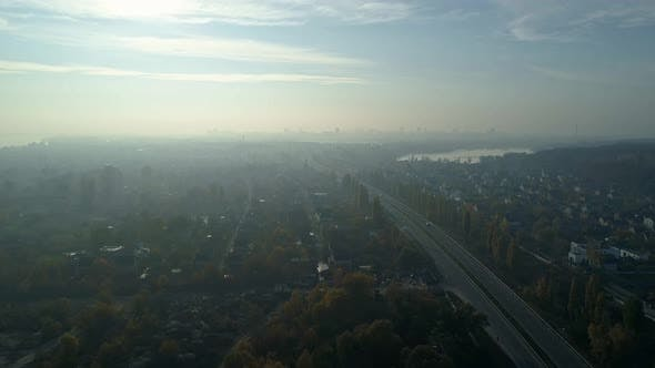 Thumbnail for Aerial Drone Footage. Fly Over Autobahn Near Downtown with City on Horizon in Light Fog.
