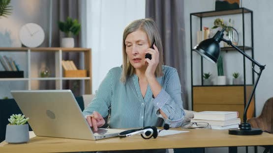 Senior Business Woman Talking on Mobile and Typing on Laptop