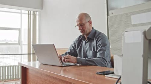 Male Mid-Adult Teacher Working on Laptop in Bright Classroom