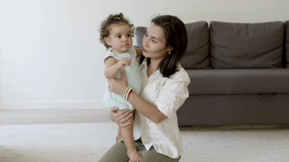 Cheerful Mom Sitting on Floor Holding Daughter in Hands