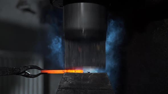 Hydraulic Hammer Shapes Piece of Hot Iron