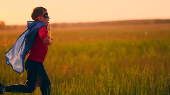 Cover Image for A Boy in a Suit and a Superhero Mask Running Across the Field at Sunset on the Grass