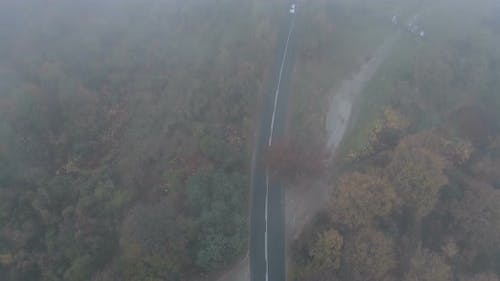 Drone Following White Car Speeding on Dark and Misty Mountain Road