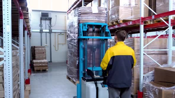 Warehouse Worker Driver in Uniform Loading Cardboard Boxes By Forklift Stacker Loader