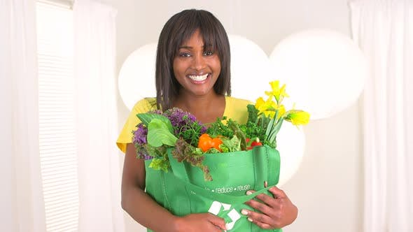 Thumbnail for Happy black woman holding groceries