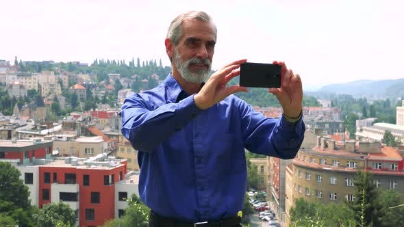 Thumbnail for Old Senior Man Takes Photos Wirh Smartphone - City (Buildings) in Background