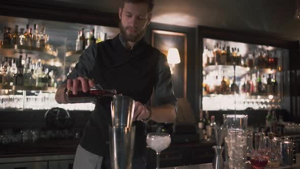 Thumbnail for Bartender Pouring Alcohol in Beaker Then in Glass with Ice, Demonstrating His Skills