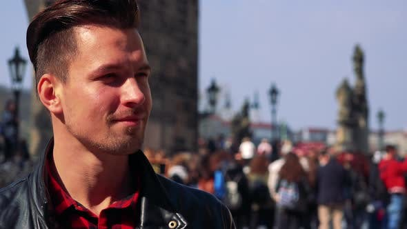 Thumbnail for A Young Handsome Man Takes Photos on a Town Square - Face Closeup - People in the Blurry Background