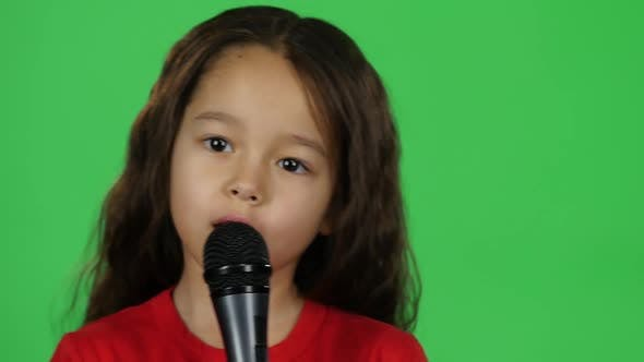 Thumbnail for Close-up Dark-haired Baby with Microphone on Green Background. Slow Motion