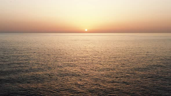 Thumbnail for Drone Flying Backwards From Atmospheric Sunset Over Rippled Sea with Birds Flying Around