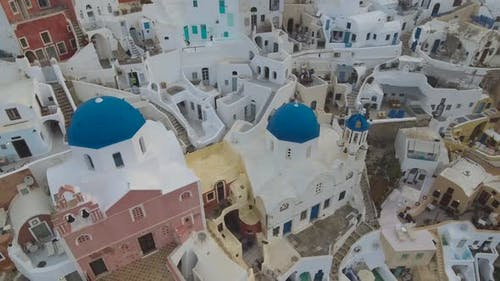 Flying over famous blue domed church in Oia on Santorini Island in Greece