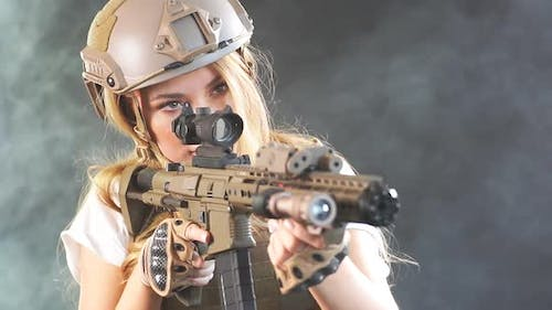 Portrait of a Beautiful Woman Warrior with Firearm in Hands, Aiming at Enemy. Slow Motion
