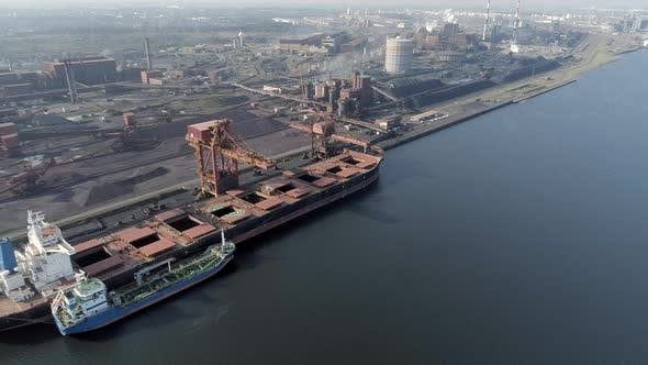 Bulk Carrier Ship Offloading Cargo at an Industrial Port in Europe