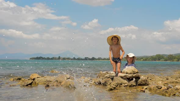 Cover Image for Tow Kids Playing with the Stones and Sea Water