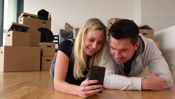 Thumbnail for A Smiling Moving Couple Lies on the Floor of an Empty Apartment and Works on a Smartphone