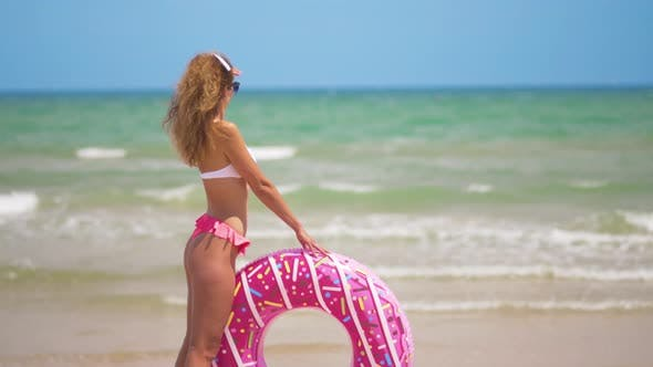 Young Woman Swimming with Inflatable Ring.