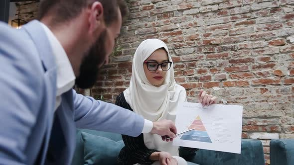 Thumbnail for Muslim Businesswoman in Glasses and in Hijab Listening Her Male Business Partner