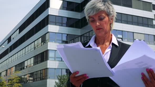 Thumbnail for Business Middle Age Woman Reads Some Business Documents - Company Building in the Background