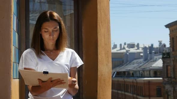Thumbnail for Porträt der jungen Frau Zeichnung mit Bleistift In Album auf Balkon in der Innenstadt