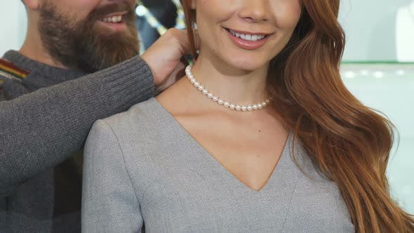 Thumbnail for Cropped Shot of a Man Adjusting Pearl Necklace on the Neck of His Wife