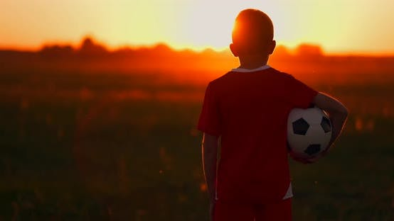 Cover Image for Boy with a Ball in a Field at Sunset, Boy Dreams of Becoming a Soccer Player, Boy Goes To the Field