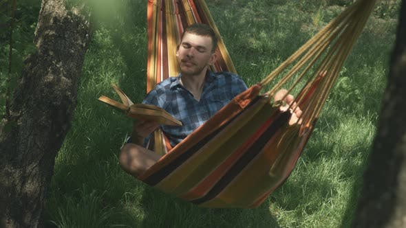 Tourist summer camping. Male tourist relaxing in hammock on vacation. Man lying on hammock outdoors