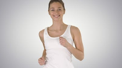 Young woman in gradient tank shirt running on gradient background.
