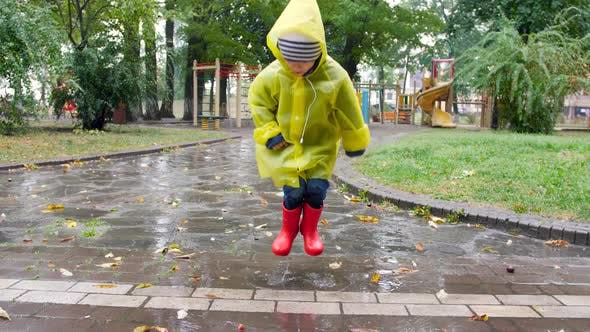 Slow Motion Video of Cheerful Little Boy in Raincoat and Wellington Boots Jumping in Puddle and