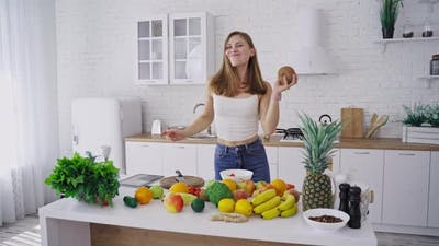 Woman with coconut in kitchen. Happy young woman in kitchen with coconut in hand