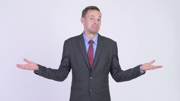 Thumbnail for Studio Shot of Businessman Shrugging Shoulders