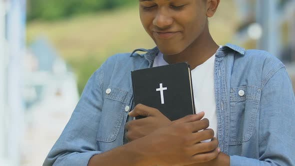 Cover Image for Teen African-American Boy Embracing Bible